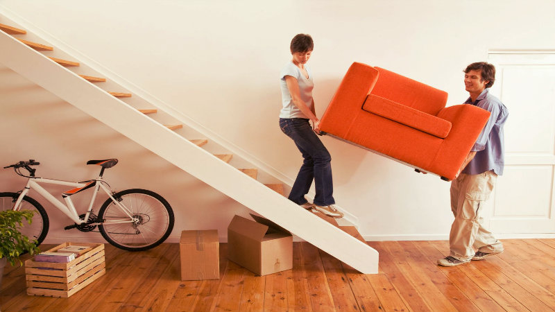 A couple moving a small couch upstairs