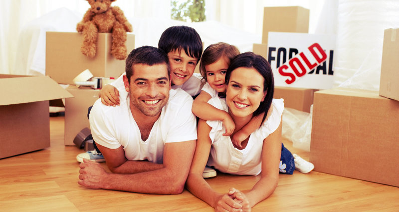 family sold home and smiling together beside packed boxes