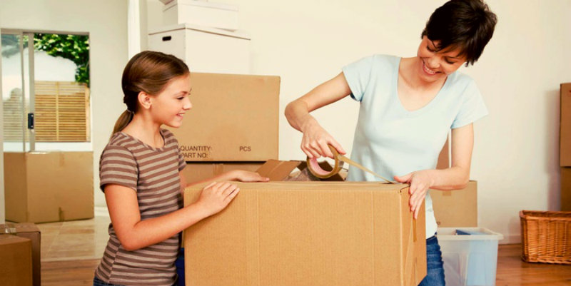 Single mum and her daughter packing boxes while smiling