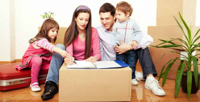 a family surrounded by packed moving boxes