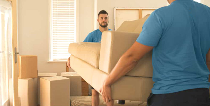 two men in blue clothes lifting furniture