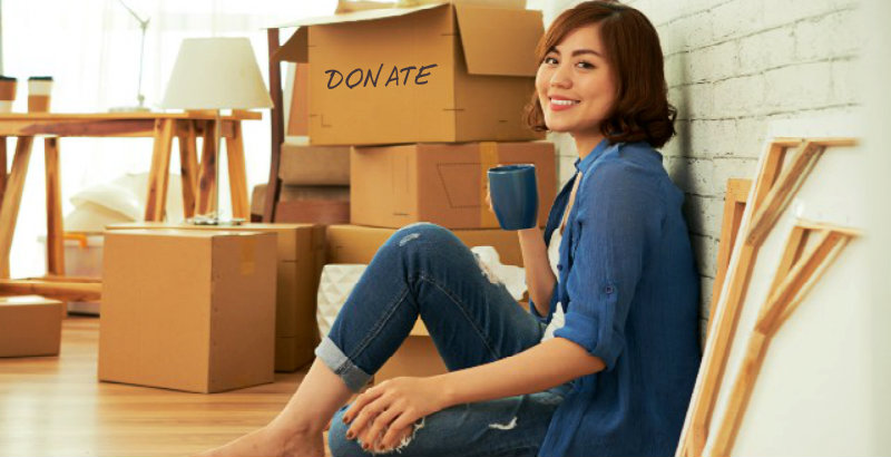 beautiful young woman drinking coffee with some packed boxes kept on floor