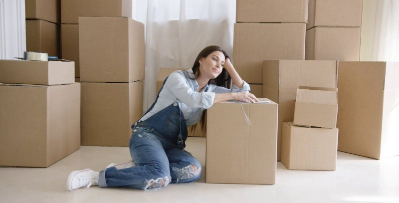 woman sitting aside packing boxes in the house
